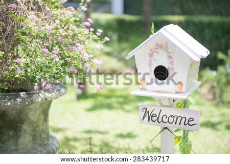 White bird house in the garden - stock photo