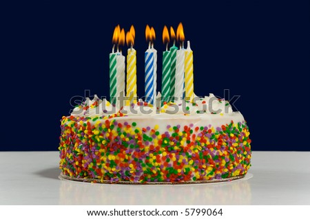White birthday cake with candy sprinkles multi-colored candles on dark blue background. - stock photo