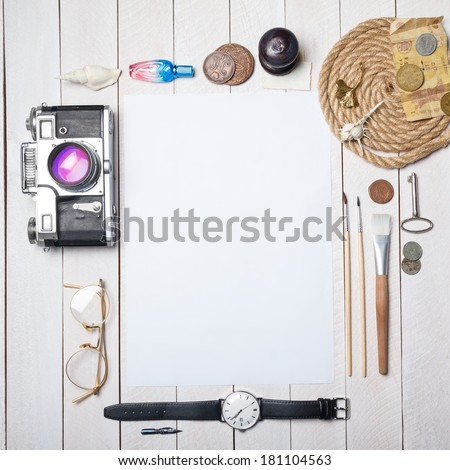 White blank paper sheet with lot of different creative stuff around it on wooden table - stock photo