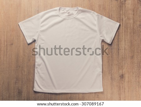 White blank t-shirt on dark wood desk. - stock photo