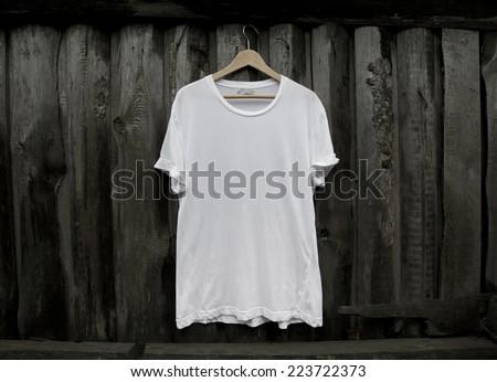 White blank t-shirt on dark wood wall - stock photo