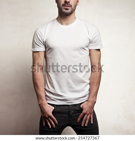White blank t-shirt on handsome athletic man, front, and concrete background - stock photo