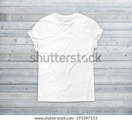 White blank t-shirt on wood background - stock photo
