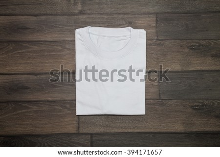 White blank t-shirt on wooden background - stock photo