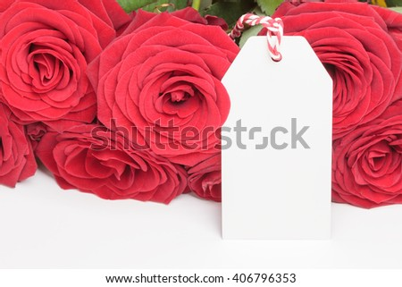 White blank tag with red roses bouquet on white background - stock photo