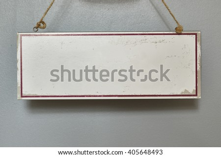 White blank wooden sign hanging on wall supported by strings. - stock photo