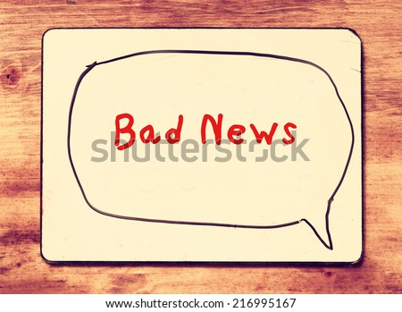 white board with the phrase bad news written on it, over wooden background. filtered image with retro effect. - stock photo