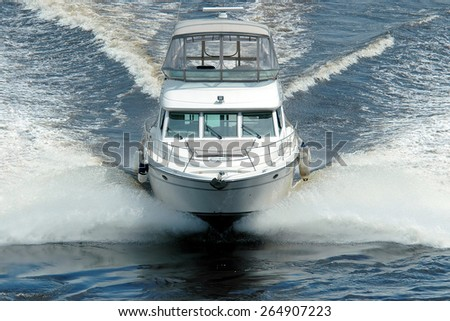 White boat floating in the waves. - stock photo