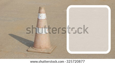 white border with old traffic cone put on the concrete road in the  sunlight. - stock photo