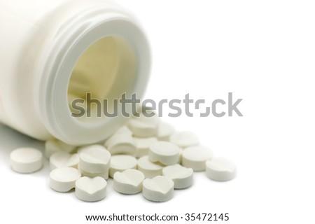 White bottle and pills macro, isolated - stock photo