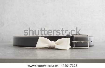 White bow tie and black leather belt on stone table. Concept of fashion for men, party dress and clothes objects. - stock photo