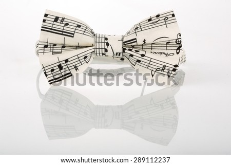 white bow tie with notes on a white background  - stock photo
