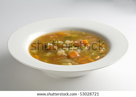 White bowl filled with vegetable soup on white - stock photo