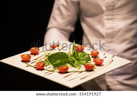 White bowl of fresh and healthy Mediterranean salad with mozzarella cheese, tomatoes and basil leaves. Caprese: cherry tomato, mozzarella balls and basil leaves.  - stock photo