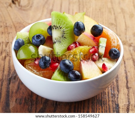 White bowl of fresh healthy fruit salad on wooden background - stock photo