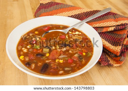 White bowl of vegetarian chili on a wood table - stock photo