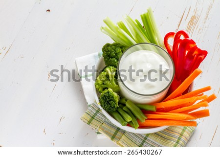 White bowl with carrot, celery, pepper, broccoli and green beans, yogurt sauce, white wood background, top view - stock photo
