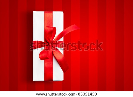 White box with a red ribbon on stripped background - stock photo