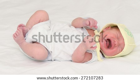 White boy full size lying on the bed crying in a yellow cap - stock photo