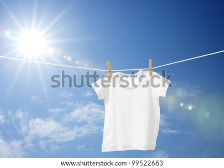 White boys T-shirt on clothes line against blue sky - stock photo