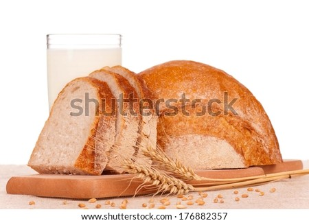 White bread slices on a chopping board with milk over white background - stock photo