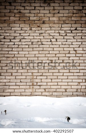 White brick wall and a ground covered with snow - stock photo
