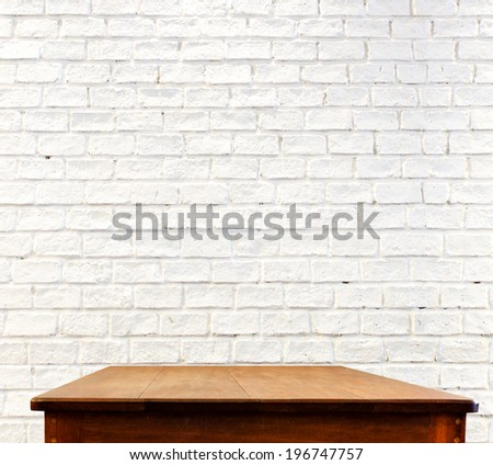 white brick wall and wooden table - stock photo