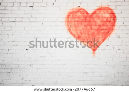 white brick wall with red heart background - stock photo