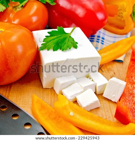 White brine cheese, black knife, parsley, tomatoes and red peppers on a wooden boards background - stock photo