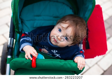 White brown haired Caucasian baby boy with head bent dressed in blue sweater looks curiously out of green stroller in spring time - stock photo