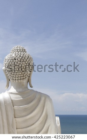 White buddha statue facing the sea - stock photo