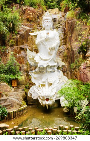 White Buddhist statue on background of small waterfall in a garden with pond of the Ten Thousand Buddhas Monastery in Hong Kong. Hong Kong is popular tourist destination of Asia. - stock photo