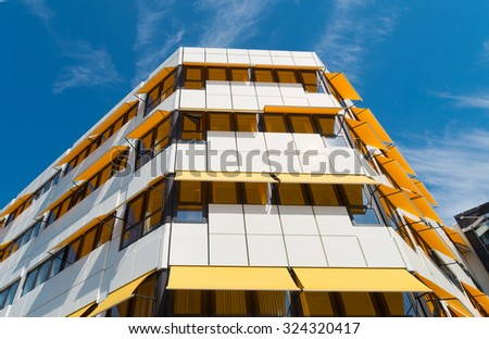 white building with yellow sunblinds - stock photo