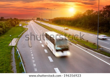 White bus in the rush hour on the highway at dusk - stock photo