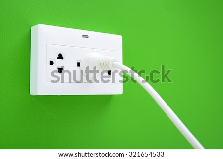 White cable plugged in a white electric outlet mounted on green wall - stock photo