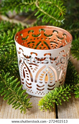 White candle holder with oriental ornaments among fir branches, christmas decor - stock photo