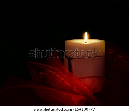 White candle in a glass holder with a red sash 2.                                - stock photo