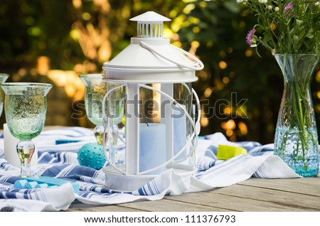 White candle lantern on a served wooden table with goblets and a vase with flowers - stock photo