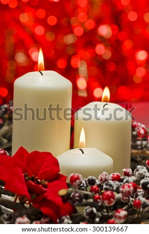 White candles in autumn winter decoration in front of a red background - stock photo