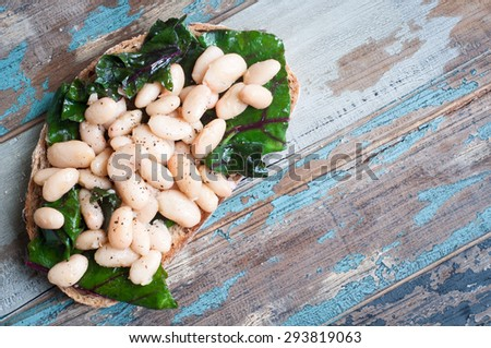 White cannellini beans, spinach and garlic on sourdough bread. A healthy vegetarian snack served on a rustic wood table. - stock photo
