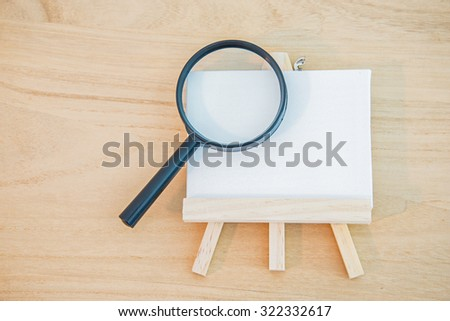 White canvas art board with magnifier glass on wood background - stock photo