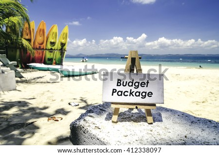 white canvas frame and wooden easel with word BUDGET PACKAGE. Tropical beach  at sunny day ,white sand,colorful kayaks and clear blue water background.(selective focus and blurred background) - stock photo