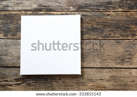 White canvas frame on a wooden background. - stock photo