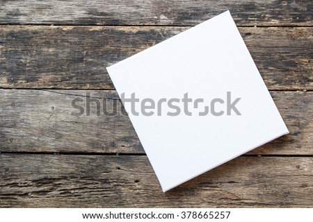 White canvas frame on a wooden background - stock photo