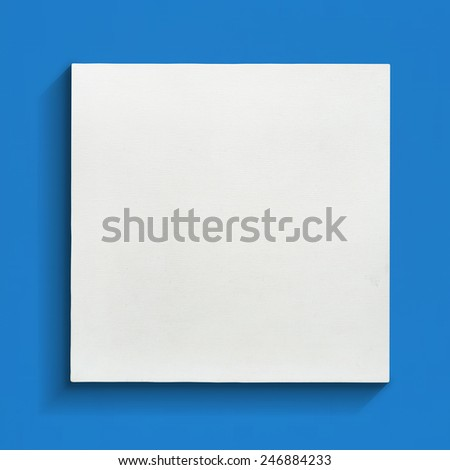 White canvas frame on blue wall background. - stock photo