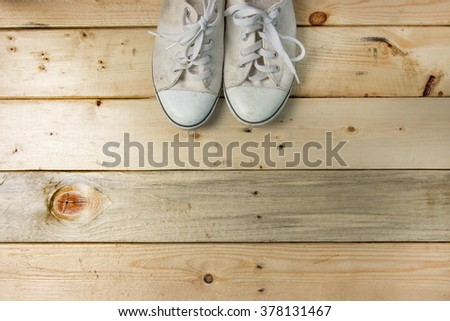 white canvas old shoe on wooden floor with space for text - stock photo
