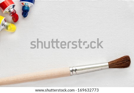 White canvas texture with paints and paintbrush - stock photo
