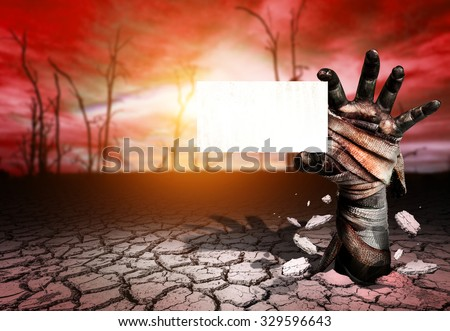 White card in Zombie hand through Soil cracked in Magic land and blurred tree die background.Halloween theme - stock photo