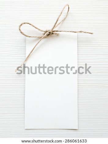 White card note with ribbon on wooden background  - stock photo