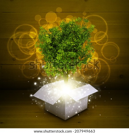 White cardboard box with magical green tree - stock photo